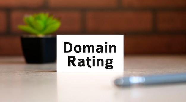 Domainbewertungstext des geschäftskonzepts auf weißer liste und mit stift und einem schwarzen topf mit einer blume dahinter