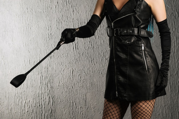 Dominante frau in einem lederkleid mit einer tracht prügel in der hand.