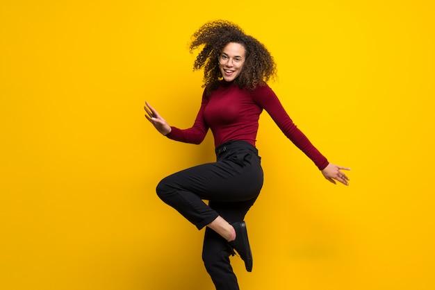 Dominikanische frau mit dem lockigen haar, das über lokalisierte gelbe wand springt