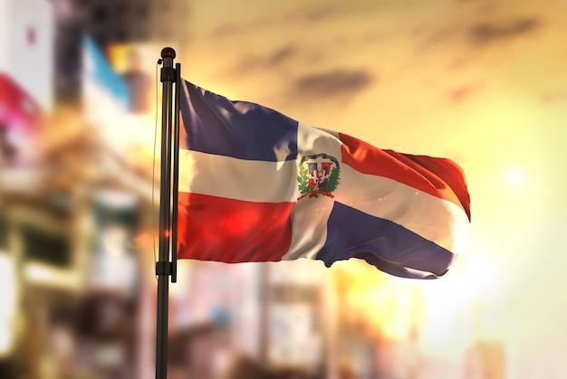Dominikanische republik flagge gegen stadt verschwommen hintergrund bei sonnenaufgang hintergrundbeleuchtung