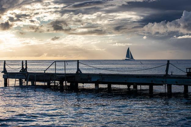 Dominikanische sonnenuntergang am pier mit leuten, die das meer beobachten
