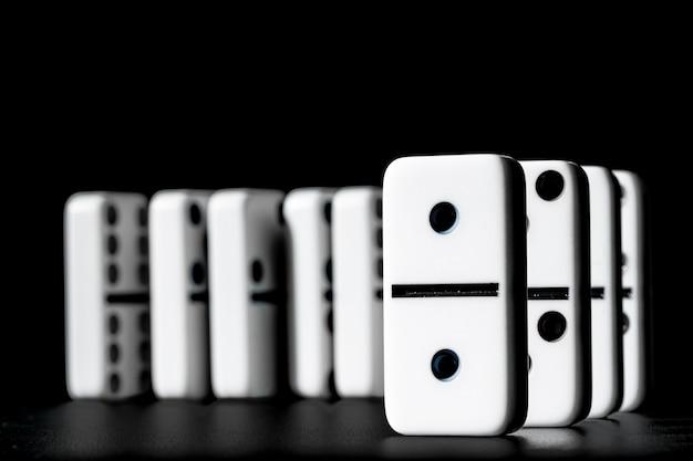 Dominos, die in folge auf schwarzem hintergrund stehen