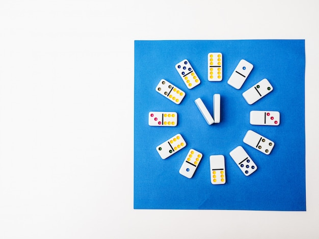 Dominouhr auf weißem blauem hintergrund. zeit zum spielen