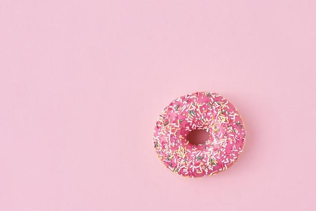 Donats dekorierte streusel und zuckerguss auf pink. kreatives und minimalistisches food-konzept, draufsicht flach