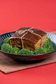 Dong po rou dongpo schweinefleisch in einem schönen blauen teller mit grünem brokkoli gemüse traditionelles festliches essen für chinesische neujahrsküche mahlzeit nahaufnahme