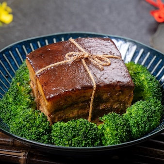 Dong po rou (dongpo schweinefleisch) in einem schönen blauen teller mit grünem brokkoli-gemüse, traditionelles festliches essen für chinesische neujahrsküche mahlzeit, nahaufnahme.