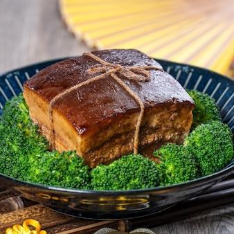 Dong po rou (dongpo-schweinefleisch) in einem schönen blauen teller mit grünem brokkoli-gemüse, traditionelles festliches essen für chinesisches neujahrsessen, nahaufnahme.