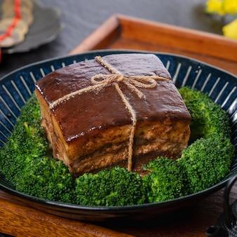 Dong po rou (dongpo schweinefleisch) in einem schönen blauen teller mit grünem brokkoli-gemüse