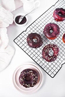 Donut auf dem backblech glasiert mit schokoladencreme oder zuckerguss. frühstückskonzept.
