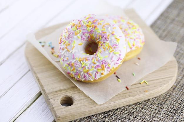Donut auf einem hölzernen weißen hintergrund und eine streuung von süßen ornamenten