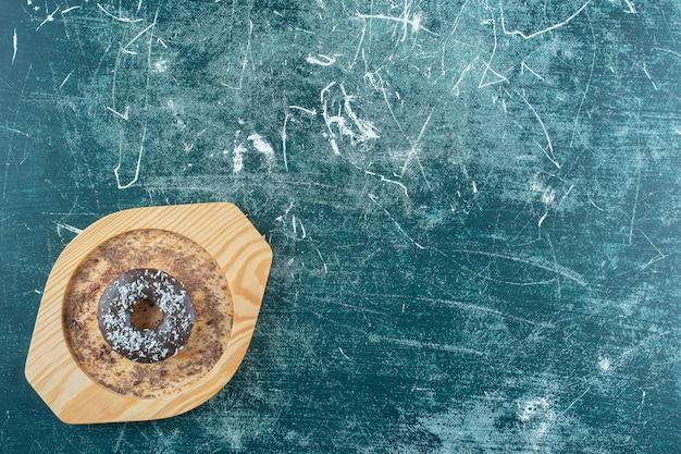 Donut auf einer holzplatte, auf blauem hintergrund. foto in hoher qualität