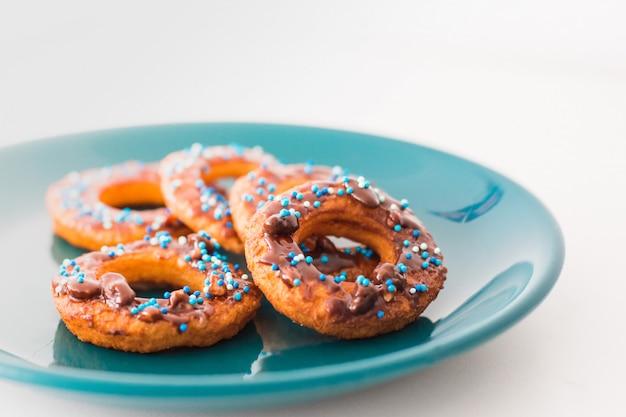 Donut auf einer platte und auf einem holztisch.