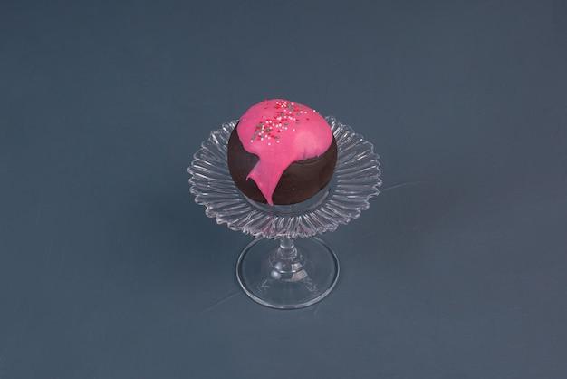 Donut auf glasplatte auf marmorhintergrund.