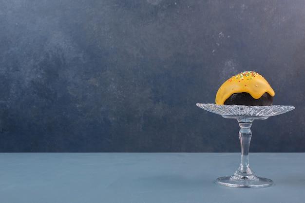 Donut auf glasplatte auf marmortisch.