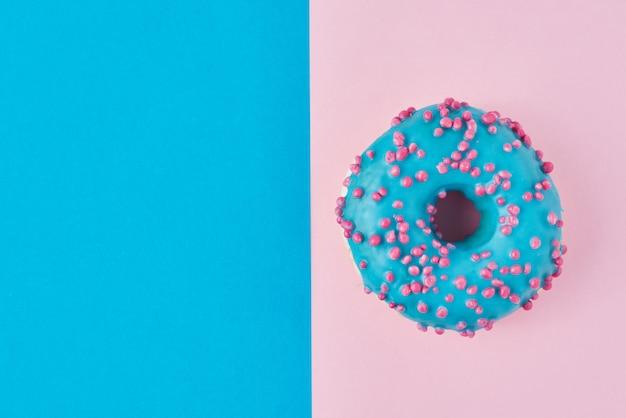 Donut auf pastellrosa und blau. minimalismus kreative lebensmittelkomposition. flacher laienstil