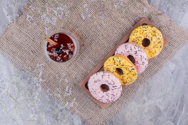 Donut brötchen auf einer holzplatte mit einer tasse glitzern