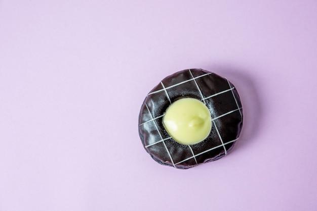 Donut chocolate cover mit schokolade und bestreuen mit donuts. legen sie auf einen rosa hintergrund.