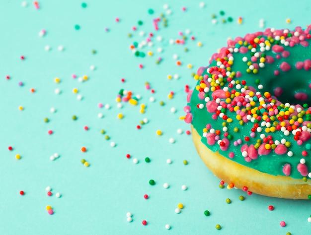 Donut (donut) in verschiedenen farben auf grünem grund mit mehrfarbigen festlichen zuckerstreuseln. urlaub und süßigkeiten, backen für kinder, zuckerkonzept
