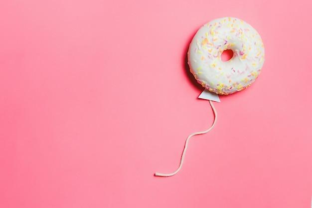 Donut in form des ballons im himmel, draufsichthintergrund