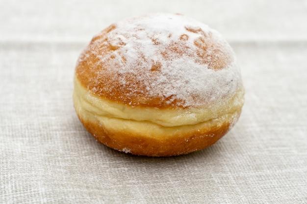 Donut in puderzuckereis auf einer hellen oberfläche