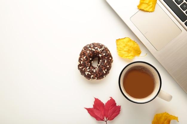 Donut, kaffeetasse und herbstlaub auf weißem hintergrund, ansicht von oben