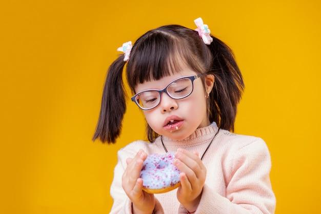 Donut mit elementen. aufmerksame junge dame mit chromosomenanomalie, die geschwollenen donut trägt, während sie krümel auf ihren lippen hat