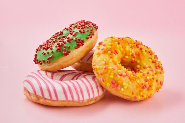 Donut mit mehrfarbiger glasur auf trendiger rosa oberfläche. donut sind traditionelles süßes gebäck. süße donuts.
