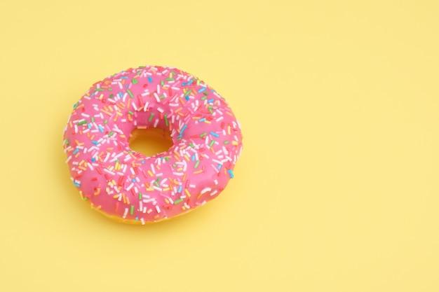 Donut mit rosa zuckerguss und gebäckstreuseln auf gelbem oberflächenkopierraum