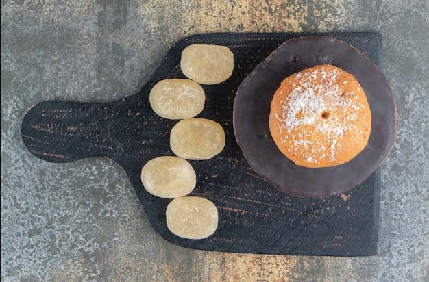 Donut mit zuckerpulver und süßen bonbons belegt
