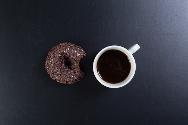 Donut und kaffee auf schwarzem hintergrund