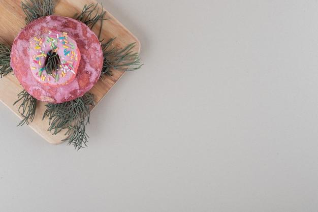 Donut und keksstapel auf kiefernblättern auf einem holzbrett auf marmorhintergrund.