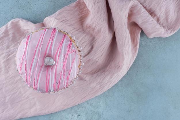 Donutbrötchen mit rosa sahne oben drauf.