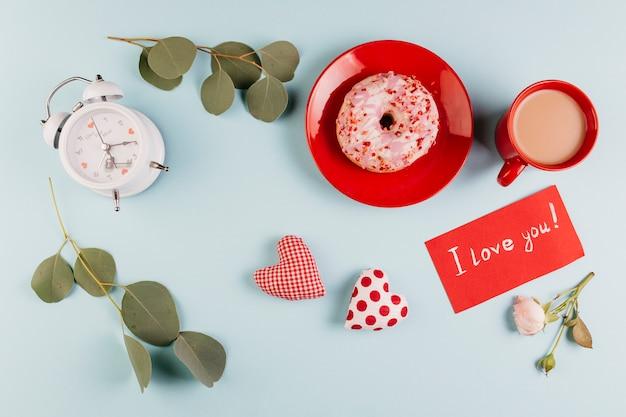 Donutfrühstück mit der anmerkung des valentinsgrußes und dekorationen