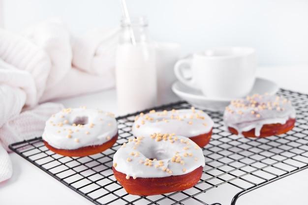 Donuts auf dem backblech glasierte weiße schokoladencreme oder zuckerguss. flasche mit milch und tasse kaffee auf dem hintergrund