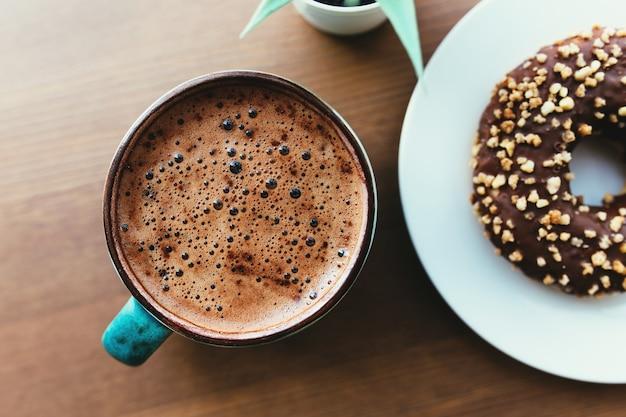 Donuts auf dem weißen teller und kaffee auf dem holztisch.