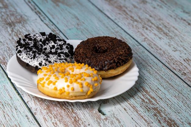 Donuts auf einem weißen teller auf einem holztisch