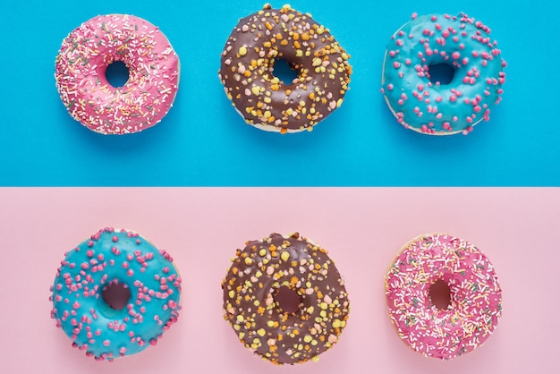 Donuts auf pastellrosa. minimalismus kreative lebensmittelkomposition. flacher laienstil