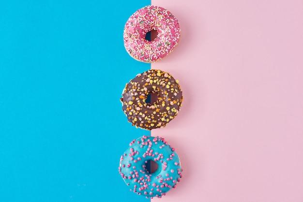 Donuts auf pastellrosa und blau. minimalismus kreative lebensmittelkomposition. flacher laienstil