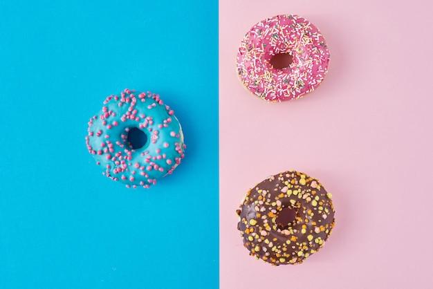 Donuts auf pastellrosa und blauem hintergrund. minimalismus kreative lebensmittelkomposition. flacher laienstil