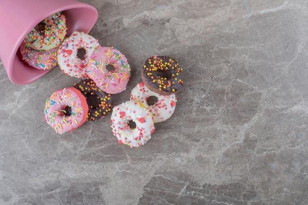 Donuts aus einer schüssel auf marmoroberfläche verschüttet