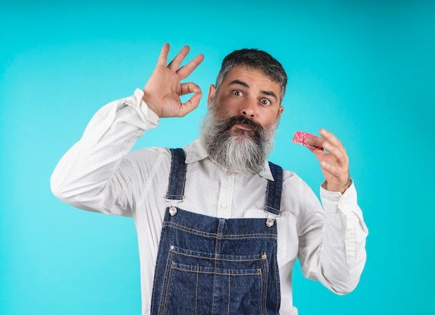 Donuts essen backwaren. süßigkeiten und kuchen. junk food. bärtiger hippie mit blauem brustschild gestikulierend mit seiner hand beim probieren süße schaumgummiringe auf einem hellblauen.