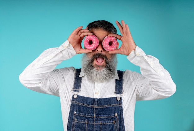 Donuts essen backwaren. süßigkeiten und kuchen. junk food. bärtiger hipster mit blauem brustschild mit süßen donuts um die augen auf einem blau-blauen.