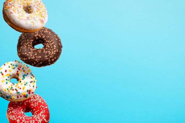Donuts fliegen in der luft auf einem blau. bäckerei, backkonzept. levitation