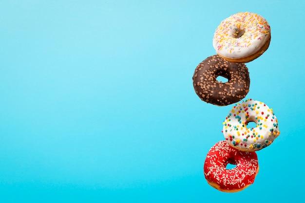 Donuts fliegen in der luft auf einem blau. bäckerei, backkonzept.