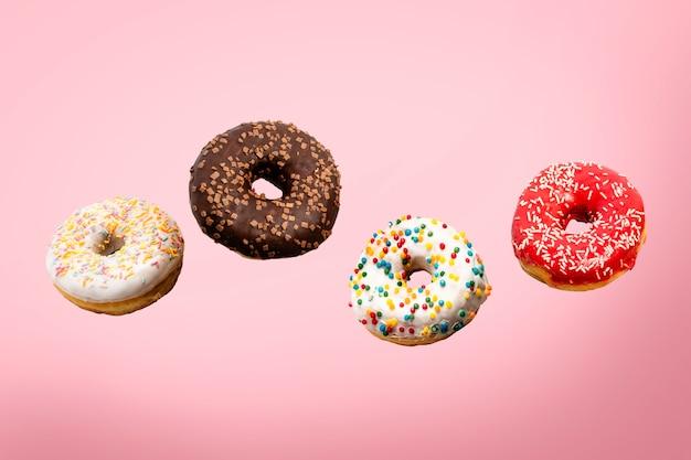 Donuts fliegen in der luft auf einem rosa. bäckerei, backkonzept.