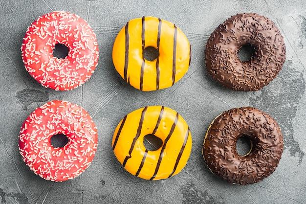 Donuts frisch gesetzt, auf grauem tisch, draufsicht flach liegen