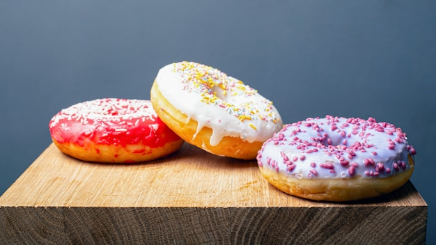 Donuts mit mehrfarbigem rotweißem und lila zuckerguss auf einem holzständer auf grauem hintergrund.