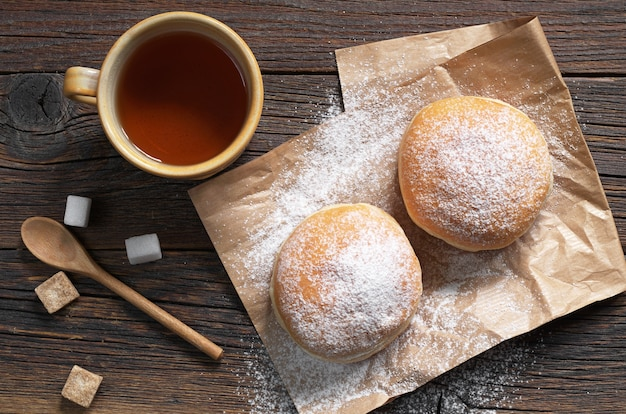Donuts mit puderzucker und einer tasse tee auf dem tisch