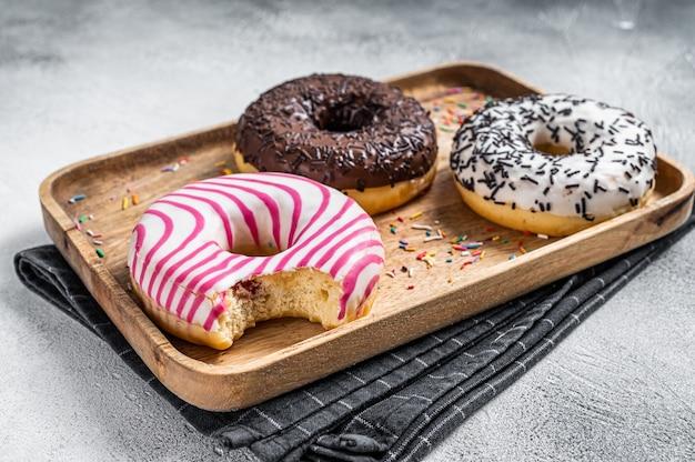 Donuts mit schokolade, rosa glasiert und besprüht donut. weißer hintergrund. ansicht von oben.