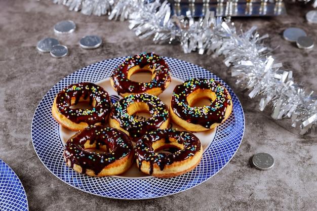 Donuts mit schokoladenglasur und streuen auf den tisch für den jüdischen feiertag von hanuka